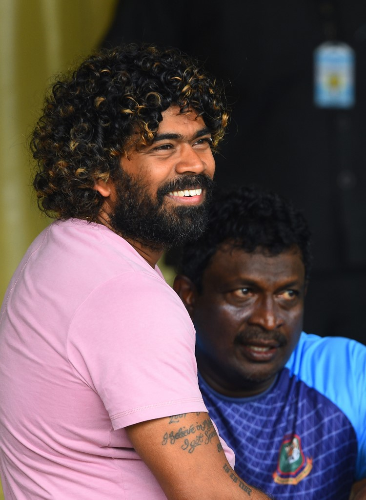 Sri Lankan cricketer Lasith Malinga (L) and Bangladesh bowling coach Champaka Ramanayake (R) look on during the one-day warm-up match between Sri Lanka Board President's XI and Bangladesh at the P. Sara Oval International cricket stadium in Colombo on July 23, 2019. - Veteran Sri Lankan pace bowler Lasith Malinga will retire from one-day international cricket with the first match of a three-match series against Bangladesh, skipper Dimuth Karunaratne said on July 22. (Photo by ISHARA S. KODIKARA / AFP)