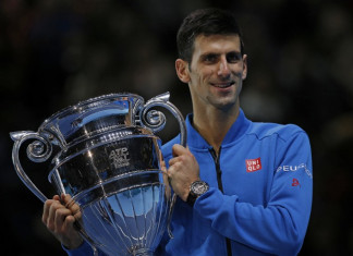 Serbia's Novak Djokovic holds the trophy of the ATP World No 1 Award after it was presented to him following his men's singles group stage match against Japan's Kei Nishikori