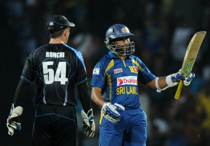 Sri Lankan batsman Tillakaratne Dilshan (R) raises his bat to the crowd after scoring a half-century (50 runs) during the second Twenty20 cricket match between Sri Lanka and New Zealand at the Pallekele International Cricket Stadium in Pallekele on November 21, 2013. AFP PHOTO/ LAKRUWAN WANNIARACHCHI / AFP / LAKRUWAN WANNIARACHCHI