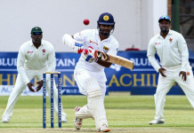 Sri Lanka's batsman Dimuth Karunaratne (C) plays a shot during the first match in a series of two cricket Test matches between Sri Lanka and hosts Zimbabwe at the Harare Sports Club on October 29, 2016. This is the 100th Test match since Zimbabwe began playing international test cricket in 1992. / AFP PHOTO / JEKESAI NJIKIZANA