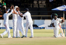 Sri Lanka's players (L) celebrate the wicket of a kneeling Donald Tiripano during the third day of the first Test match in a series of two cricket matches between Sri Lanka and Zimbabwe at the Harare Sports Club, October 31, 2016.