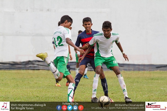 Jerold Meloginus (L) prepares to chip the ball to a forward while Abishek Fernando blocks the opponent - Schools Football 2016