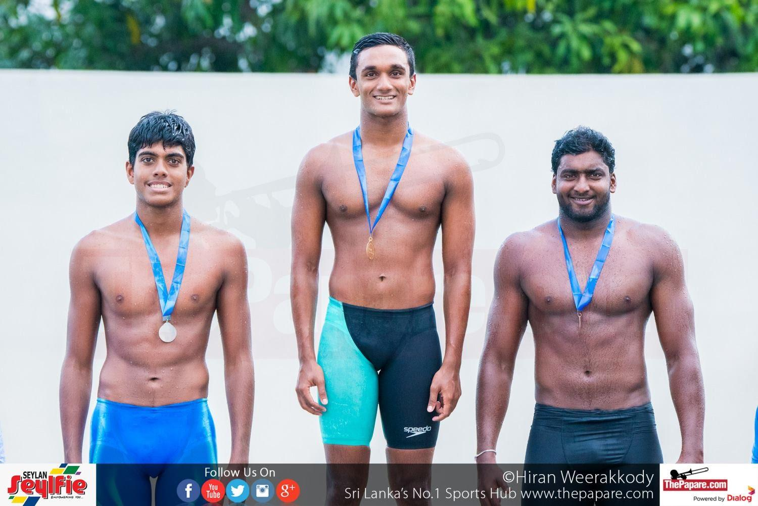 Akalanka Peiris (M) receiving his medal for 50m Butterfly as (L) R. P. De Silva (Silver) of Lyceum Wattala and K P Manawadu (Bronze) of Navy looks by